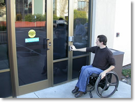 Picture of man in wheelchair is pushing button to enter the building.